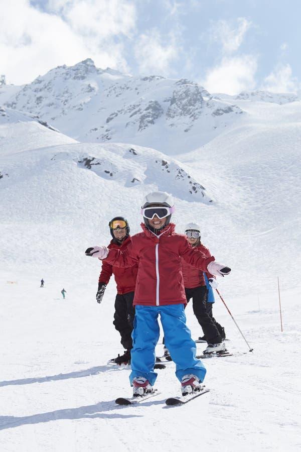 Familjen skidar på ferie i berg royaltyfria foton