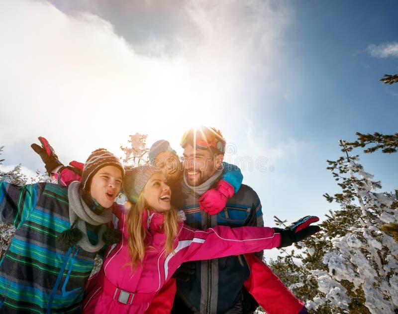 Familjen skidar på ferie i berg som har gyckel arkivfoton