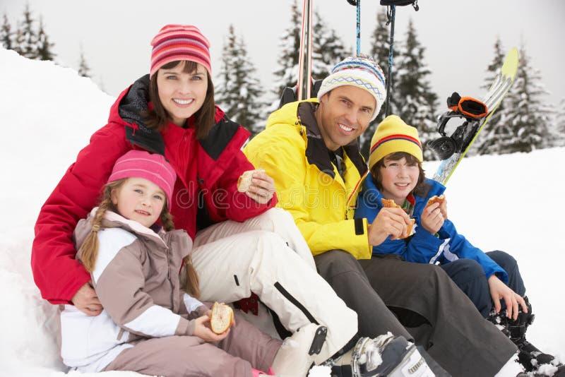 Familjen som äter smörgåsen skidar på, ferie i berg royaltyfri fotografi