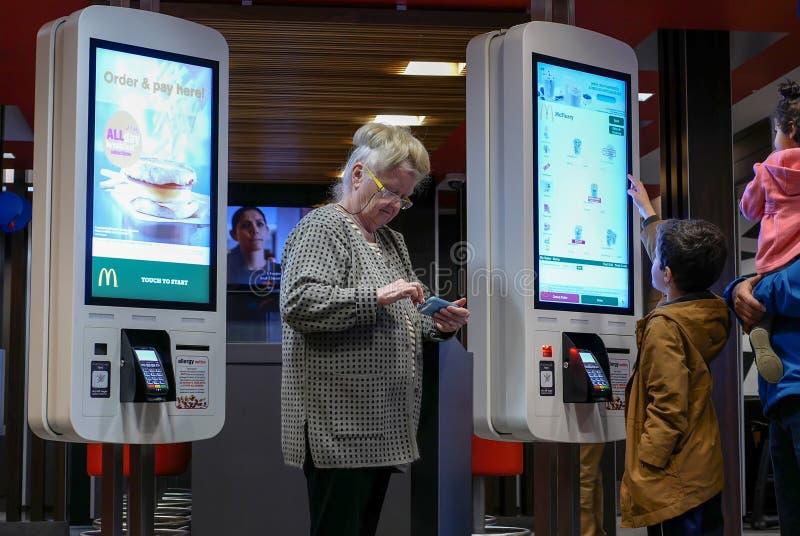 Familjen som beställer mat på självkontrollen ut, bearbetar med maskin och den gamla damen som spelar mobiltelefonen royaltyfri fotografi