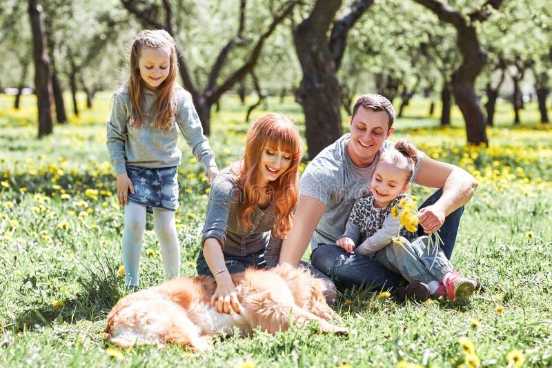 Familjen som daltar deras husdjur f?r, g?r royaltyfri bild