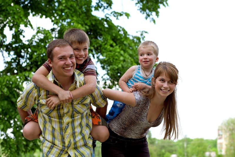 familjen som ger lycklig ridtur på axlarna, rider sons två barn arkivfoton