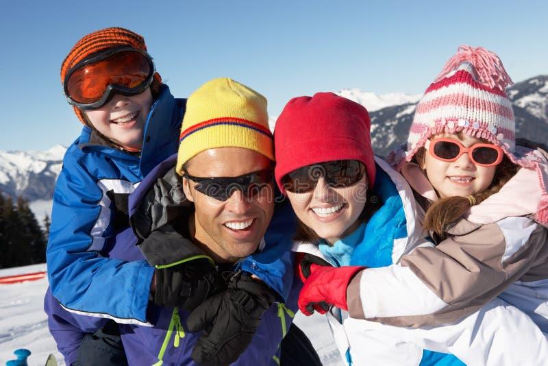 Familjen som har gyckel skidar på, ferie i berg royaltyfria foton