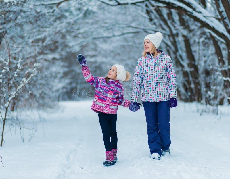 Familjen som har gyckel, spelar och skrattar på snöig vinter, går i natur arkivbilder