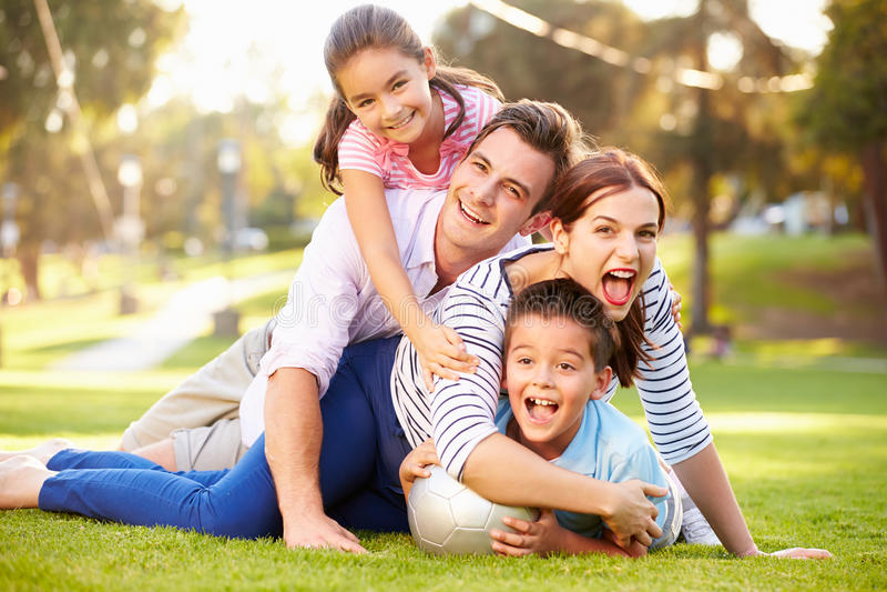 Familjen som ligger på gräs parkerar in, tillsammans fotografering för bildbyråer