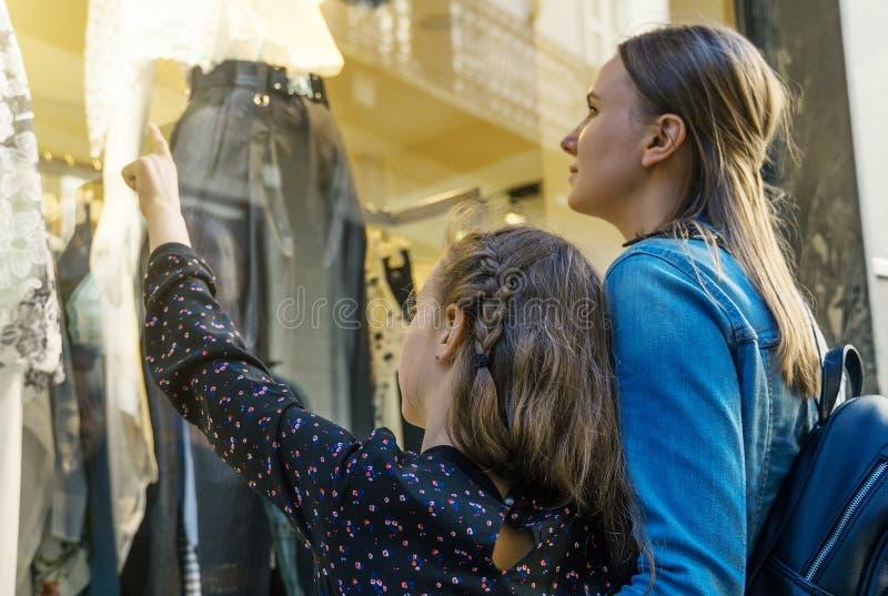Familjen som ser, shoppar fönstret royaltyfria bilder