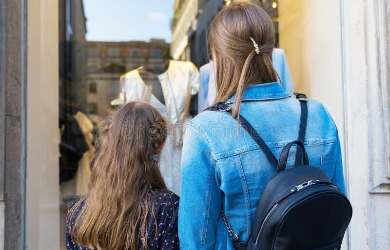 Familjen som ser, shoppar fönstret arkivfoton
