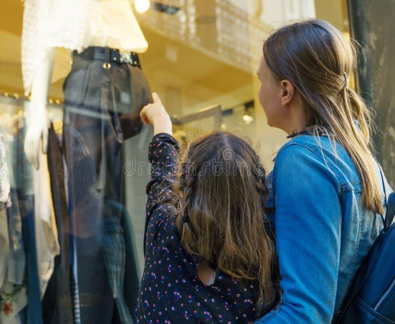 Familjen som ser, shoppar fönstret royaltyfri foto