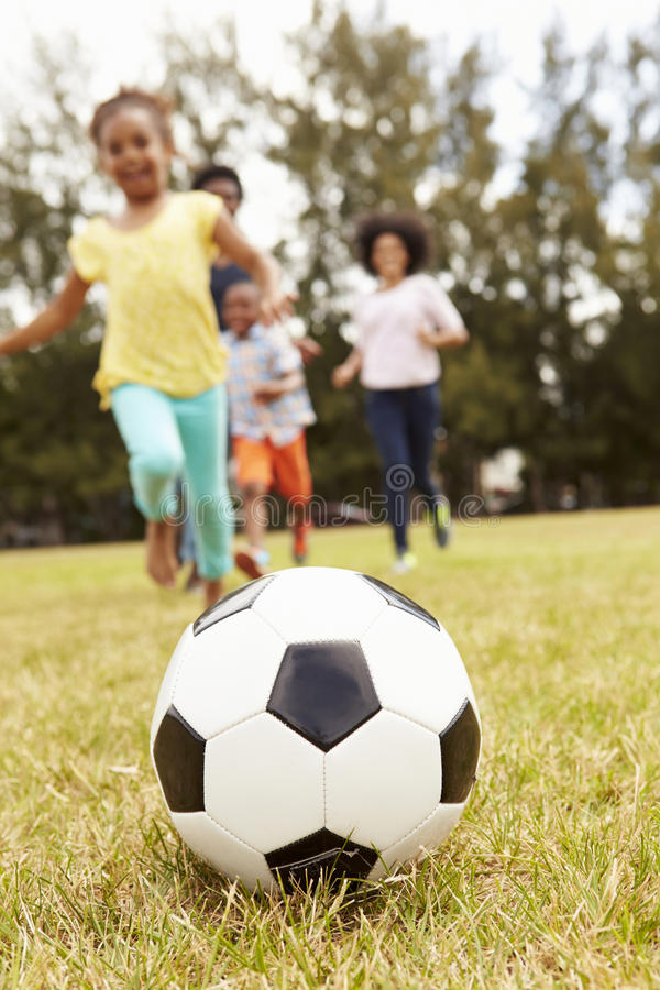 Familjen som spelar fotboll parkerar in, tillsammans arkivbild