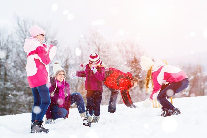 Familjen som spelar i snö som har kamp med, kastar snöboll arkivbild