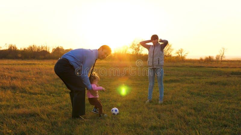 Familjen som spelar med mer ung, behandla som ett barn med fotbollbollen i parkerar på solnedgången Lycklig farsa- och barnsparkb fotografering för bildbyråer