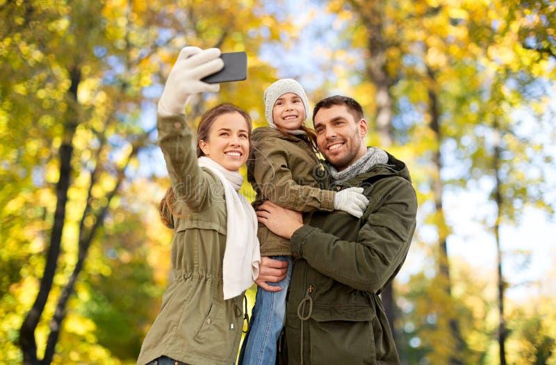 Familjen som tar selfie vid smartphonen i h?st, parkerar royaltyfria foton