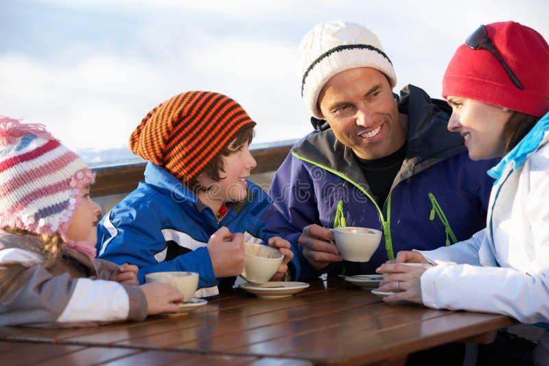Familjen som tycker om den varma drinken i Cafe på, skidar semesterorten fotografering för bildbyråer