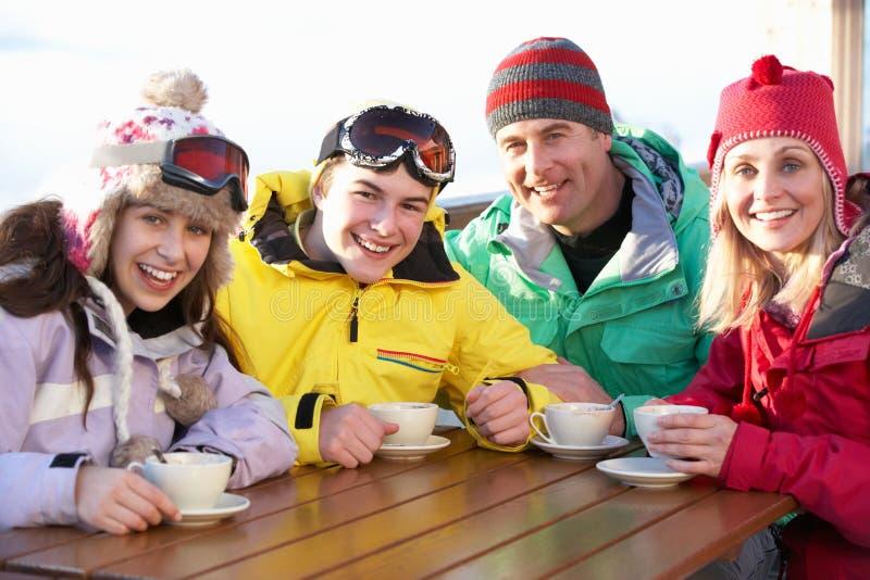 Familjen som tycker om den varma drinken i Cafe på, skidar semesterorten royaltyfria bilder