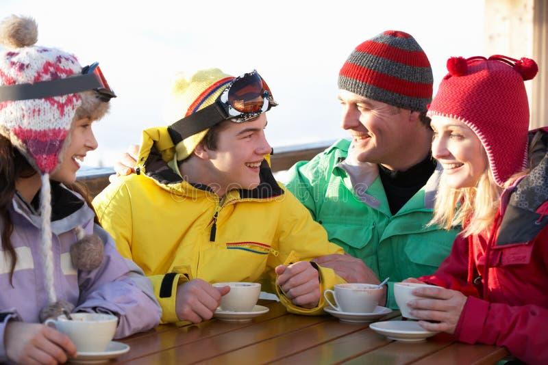 Familjen som tycker om den varma drinken i Cafe på, skidar semesterorten royaltyfri bild