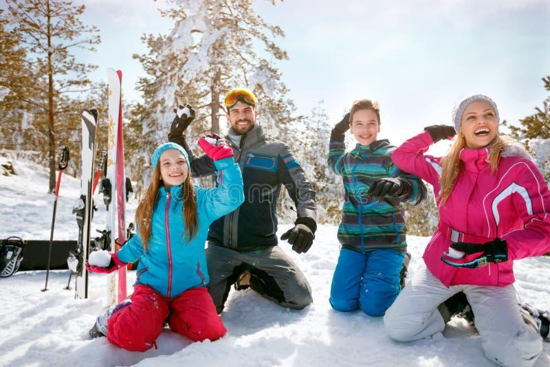 Familjen som tycker om vinter, semestrar i berg Skidar snöar solen, royaltyfria foton