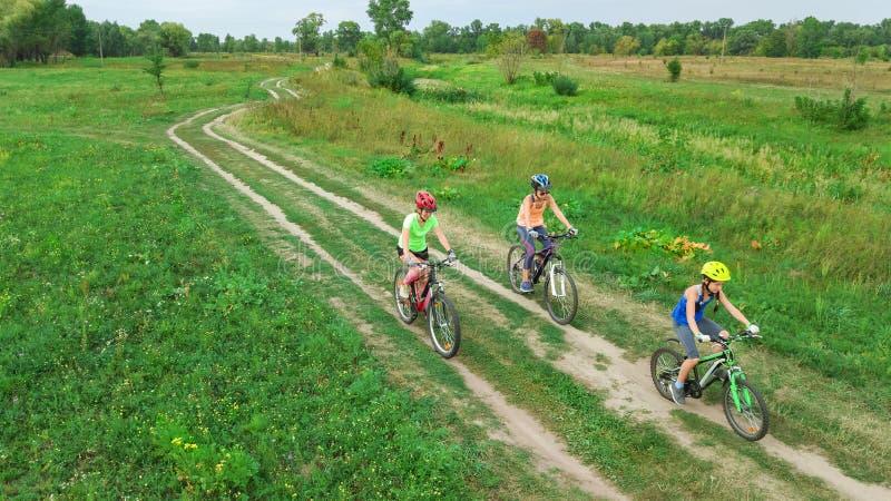 Familjen som utomhus cyklar på flyg- sikt för cyklar från över, den lyckliga aktiva modern med barn, har gyckel, familjsport royaltyfri fotografi