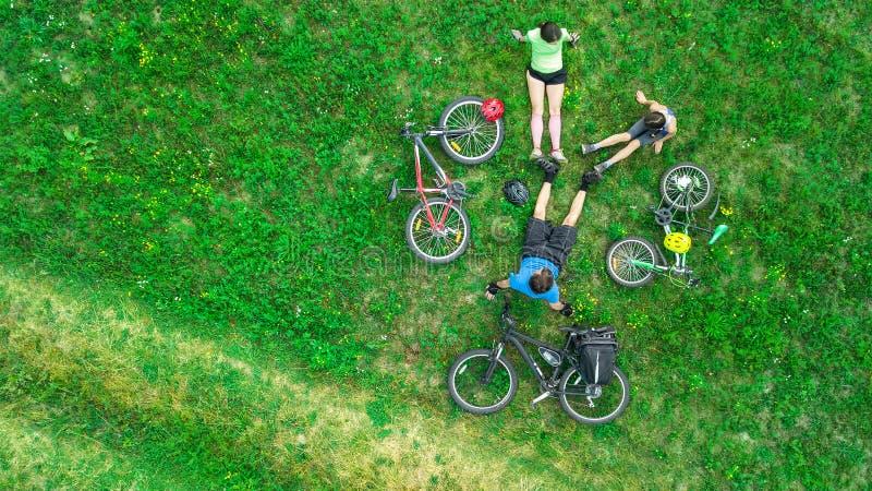 Familjen som utomhus cyklar på flyg- sikt för cyklar från över, lyckliga aktiva föräldrar med barnet, har gyckel och kopplar av p arkivfoto