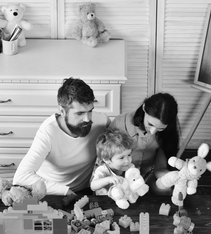 Familjen spelar begrepp Lura pojke-, moder- och faderlekbyggmästare i barnkammare royaltyfri foto
