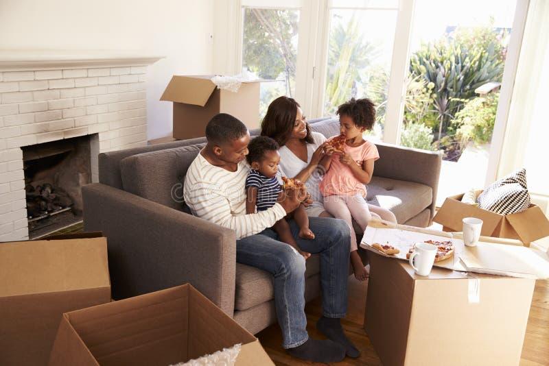 Familjen tar ett avbrott på den Sofa With Pizza On Moving dagen fotografering för bildbyråer