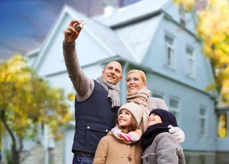 Familjen tar höstselfie vid kameran över hus arkivfoton