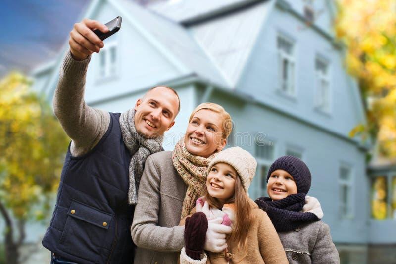 Familjen tar höstselfie vid mobiltelefonen över hus royaltyfri foto