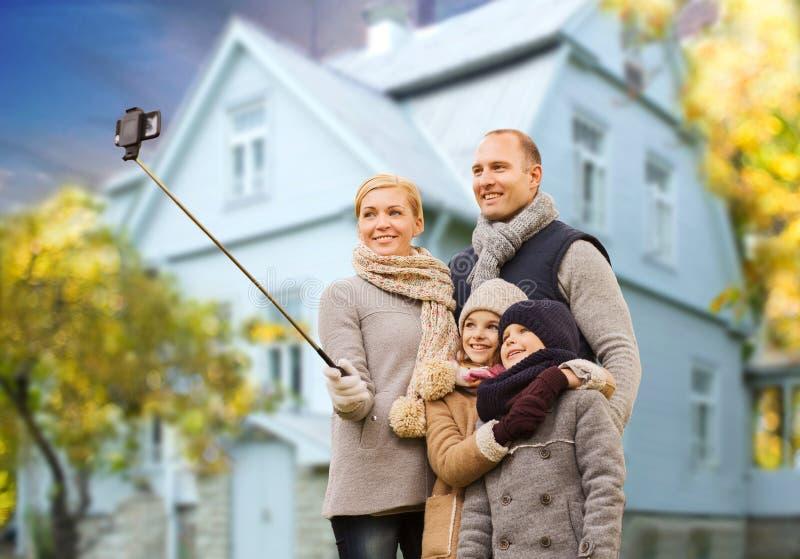 Familjen tar höstselfie vid mobiltelefonen över hus arkivfoton