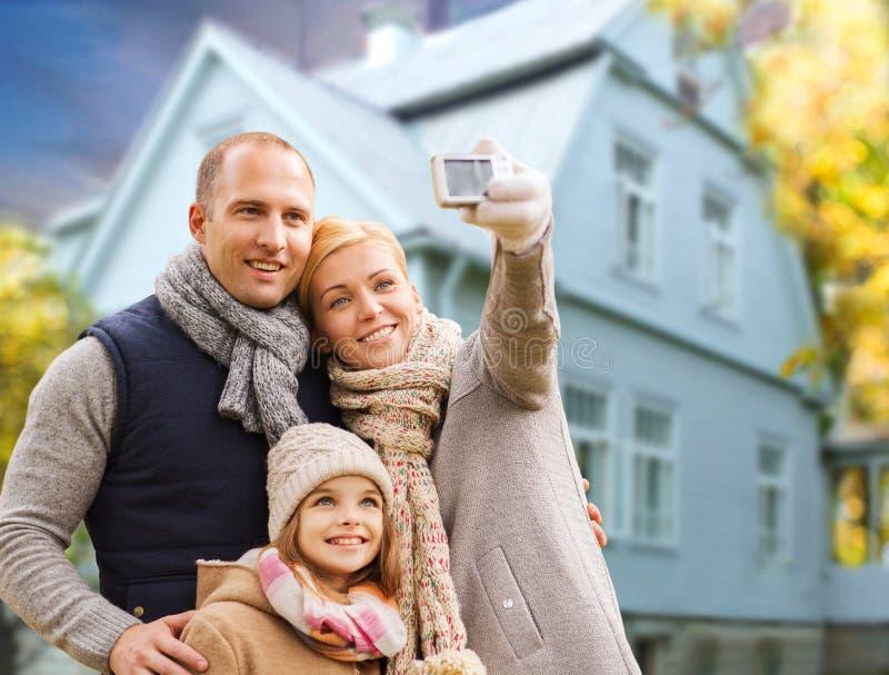 Familjen tar höstselfie vid mobiltelefonen över hus royaltyfria foton