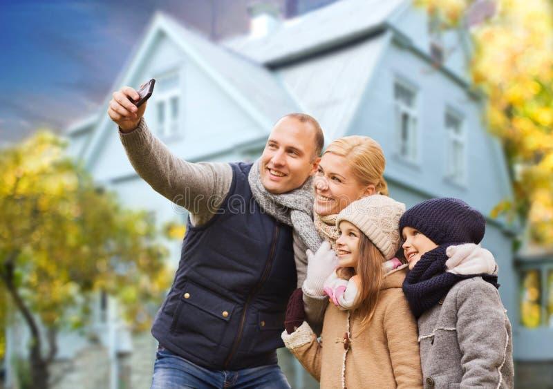 Familjen tar höstselfie vid mobiltelefonen över hus royaltyfri fotografi