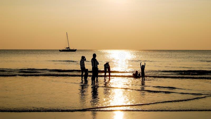 Familjen välkomnar solnedgången på stranden arkivbild