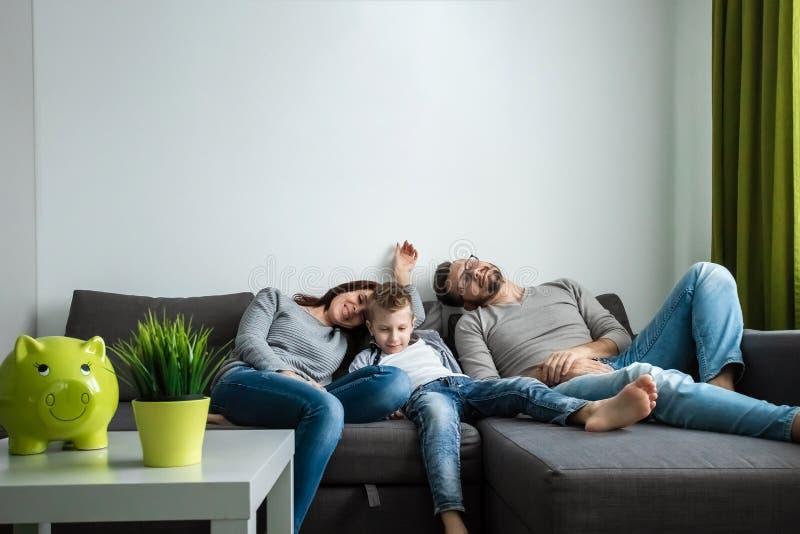 Familjen vilar på den all soffan tillsammans Begrepp av att spendera tid tillsammans, lycklig familj royaltyfri bild