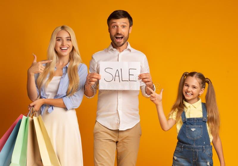 Familjepresentationer vid försäljningsskylt som håller försäljningssäckar, Studio Shot fotografering för bildbyråer