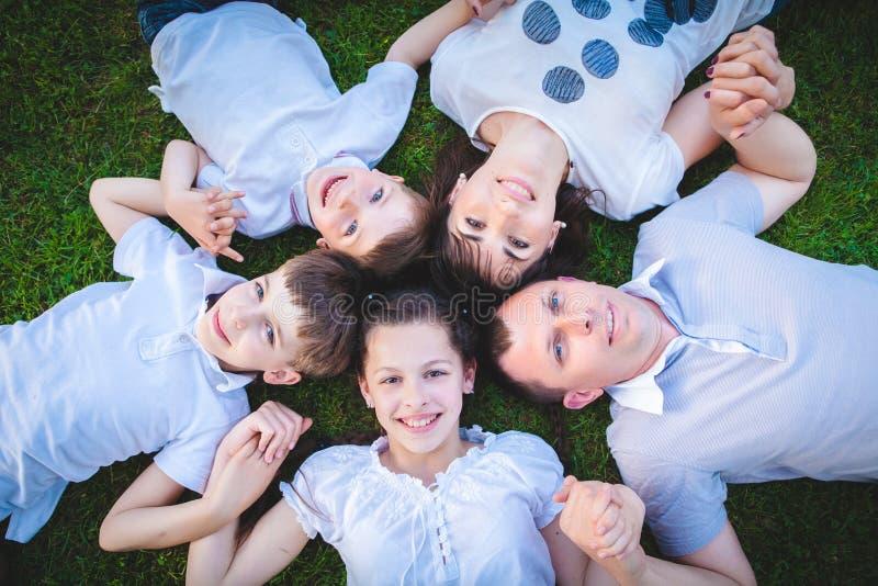 Familjer med barn som ligger på gräset arkivfoto