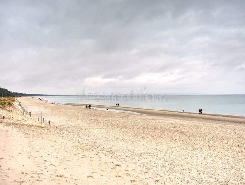 Familjer och vänner som tillsammans spenderar dag på stranden arkivbilder