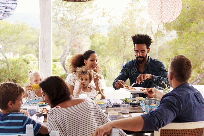 Familjer som tillsammans tycker om utomhus- mål på terrass arkivfoton