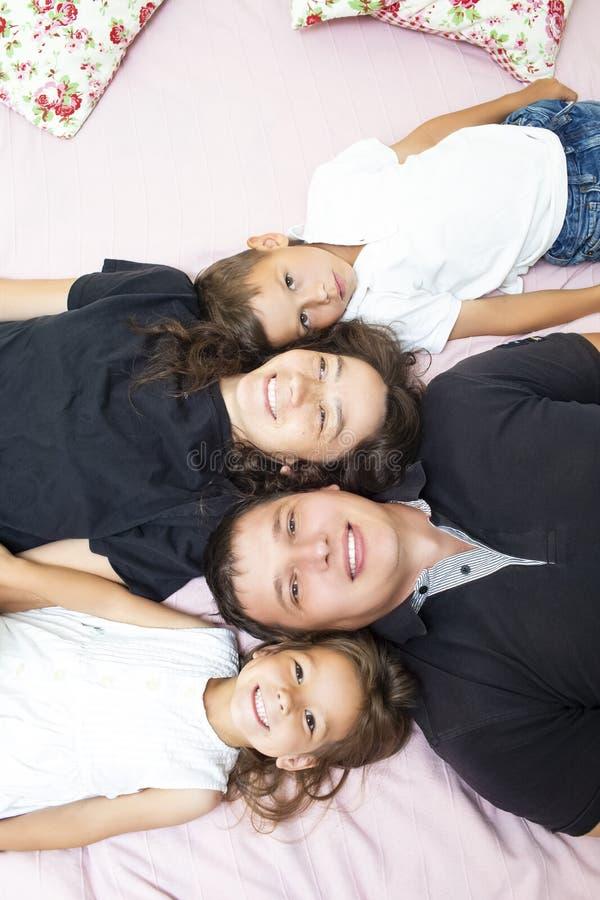 Familjevärderingar Lycklig Caucasian familj av fyra som har gyckel, medan ligga på Sofa Indoors arkivfoton
