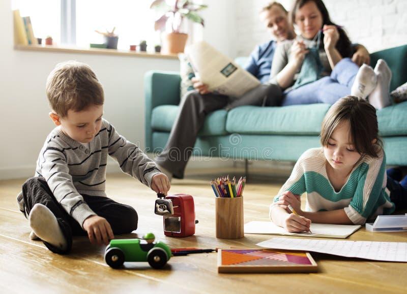 Familjförälskelseföräldrar övervakar små barn arkivbild