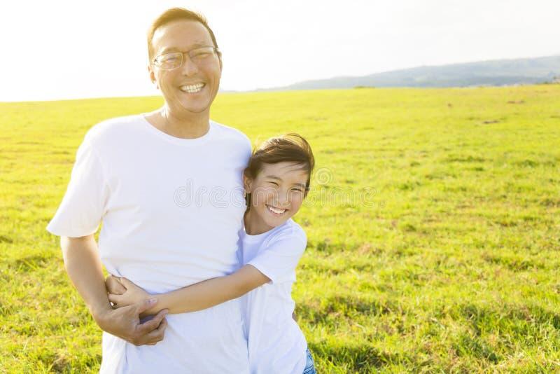 Familjfader och barn som kramar på äng arkivbild