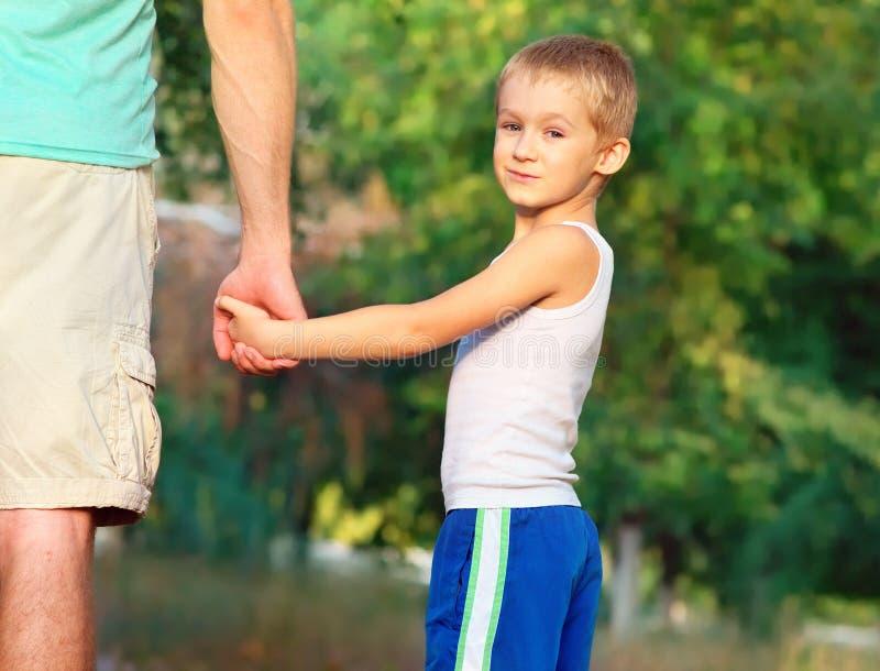 Familjfadern Man och handen för innehav för sonpojkebarn - in - räcker utomhus- lyckasinnesrörelse royaltyfri bild