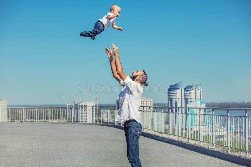Familjfarsan och behandla som ett barn lyckligt med leenden tillsammans i parkeraoverlen arkivbild