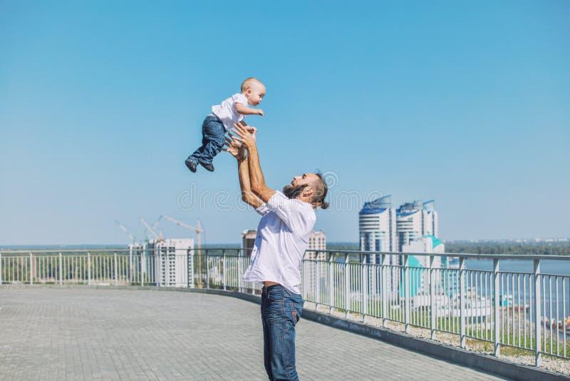 Familjfarsan och behandla som ett barn lyckligt med leenden tillsammans i parkeraoverlen arkivfoton