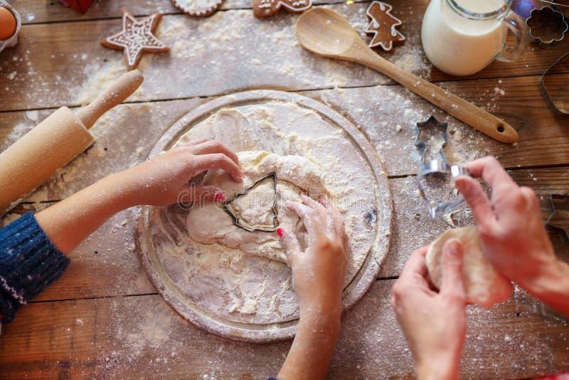 Familjferieaktivitet Bästa sikt av moders och unges händer som gör julgrankakor Lekmanna- lägenhet royaltyfri bild