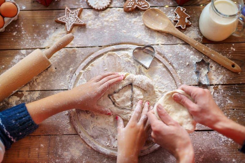Familjferieaktivitet Bästa sikt av moders och unges händer som gör julgrankakor Lekmanna- lägenhet royaltyfri foto