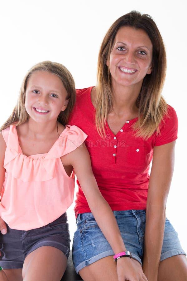 Familjflickamoder och nätt dotter på vit royaltyfria bilder