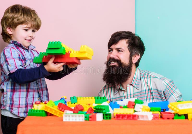 Familjfritid Fadersonlek Fadern och sonen skapar konstruktioner Sk?ggig man- och sonlek tillsammans Varje farsa och arkivbild