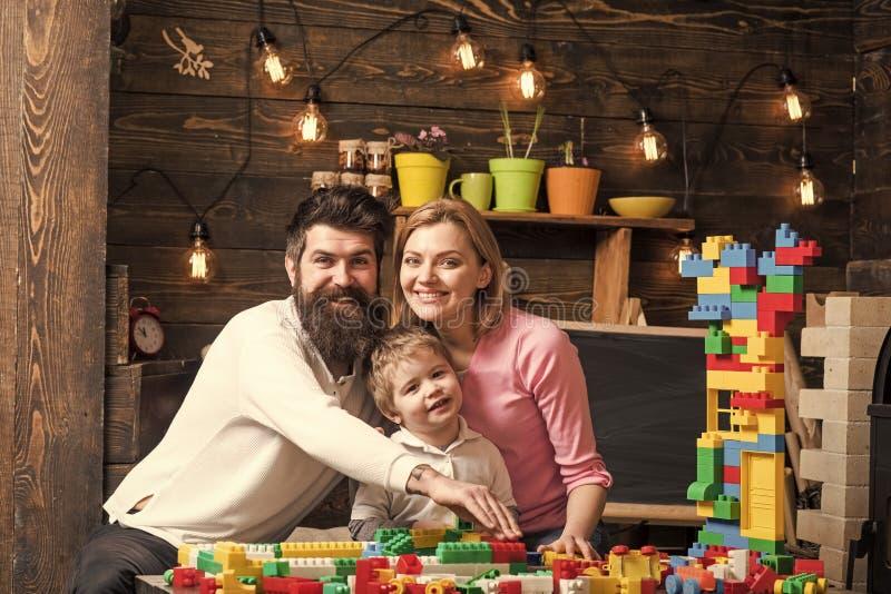 Familjfritidbegrepp Förälderkramar, den hållande ögonen på sonen som spelar, tycker om föräldraskap Unge med förälderlek med plas arkivbild
