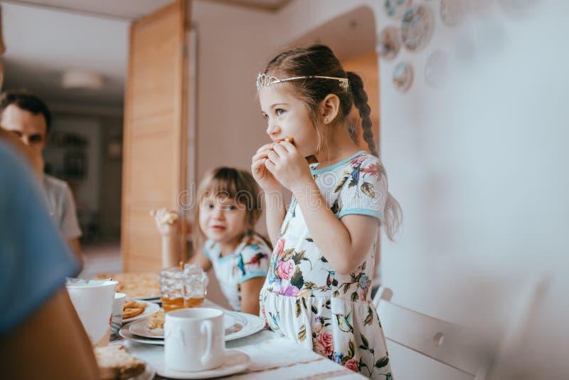 Familjfrukost hemma i det trevliga hemtrevliga köket Moder, fader och deras två döttrar som äter pannkakor royaltyfria foton