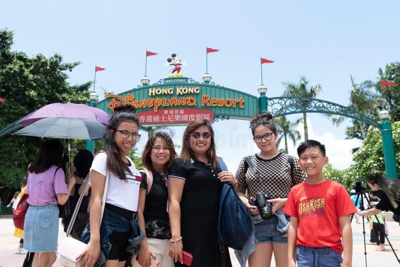 Familjgrupp som framme poserar för roligt av ingången Hong Kong för DisneyLand semesterorttecken royaltyfria bilder