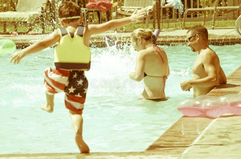 Familjgyckel på den lokala simbassängen arkivbilder