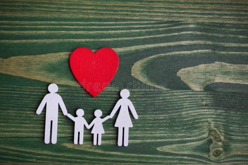 Familjhälsa, livförsäkringbegrepp Träkedja i form av familjen med röd hjärta Bästa sikt, lekmanna- lägenhet royaltyfria foton